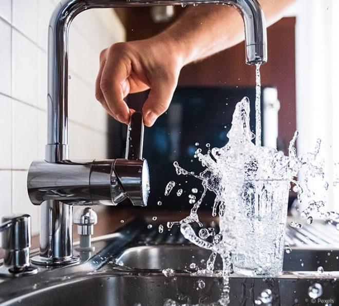 Wasserhahn wird über einem Spülbecken geöffnet. Der Wasserverbrauch ist enorm, da das Wasser aus einem überfüllten Glas herausspritzt.