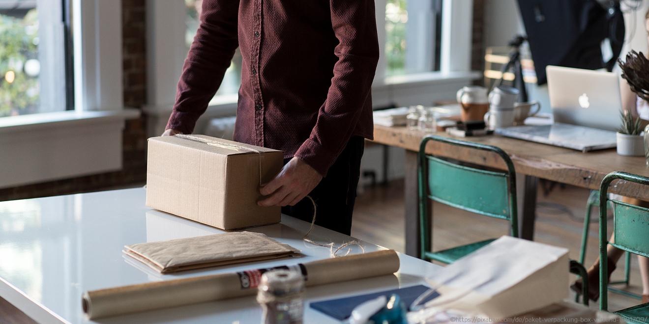 Person beim Einpacken eines Paketes