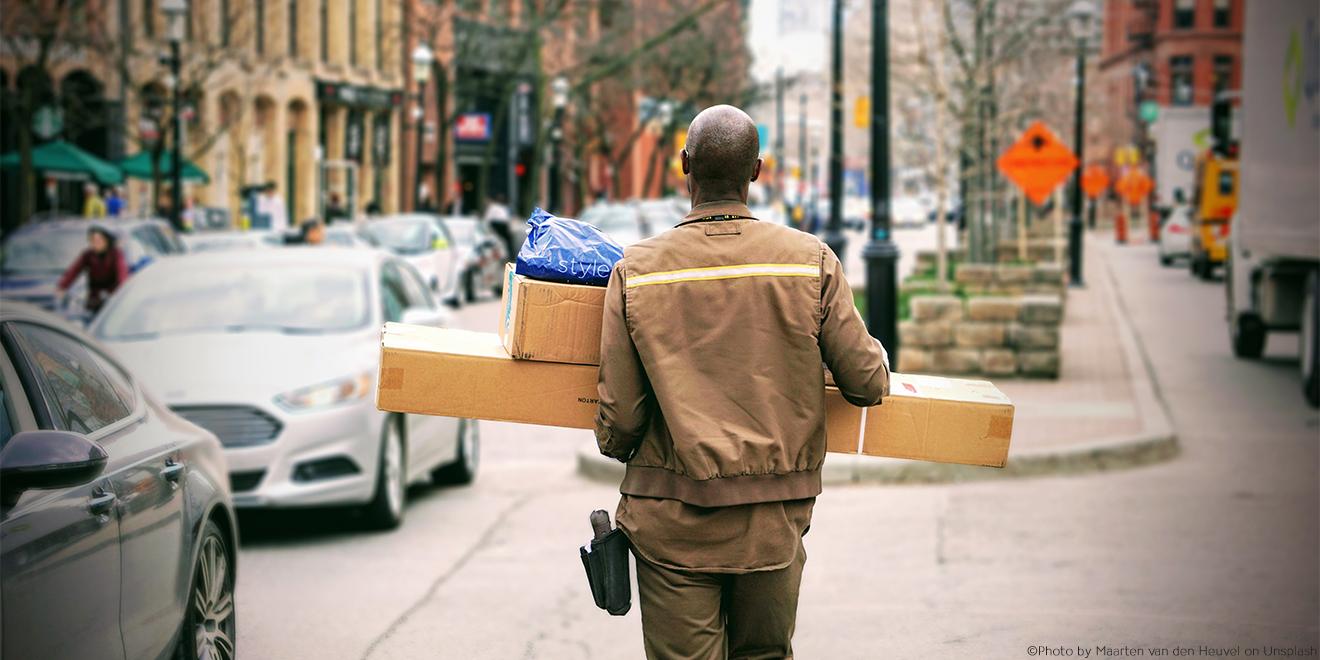 Lieferant läuft durch die Straßen mit Paket und Kleidungsstück