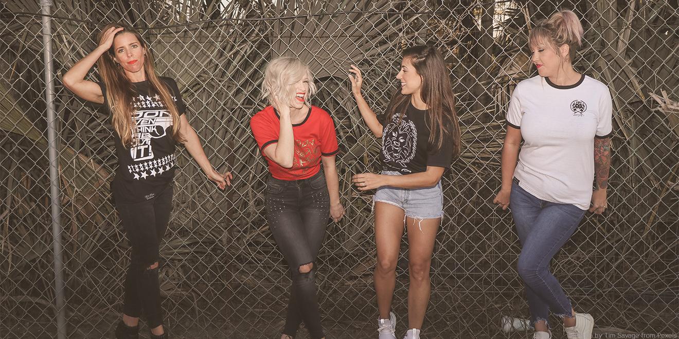 Freundinnen stehen am Zaun und präsentieren ihre Outfits
