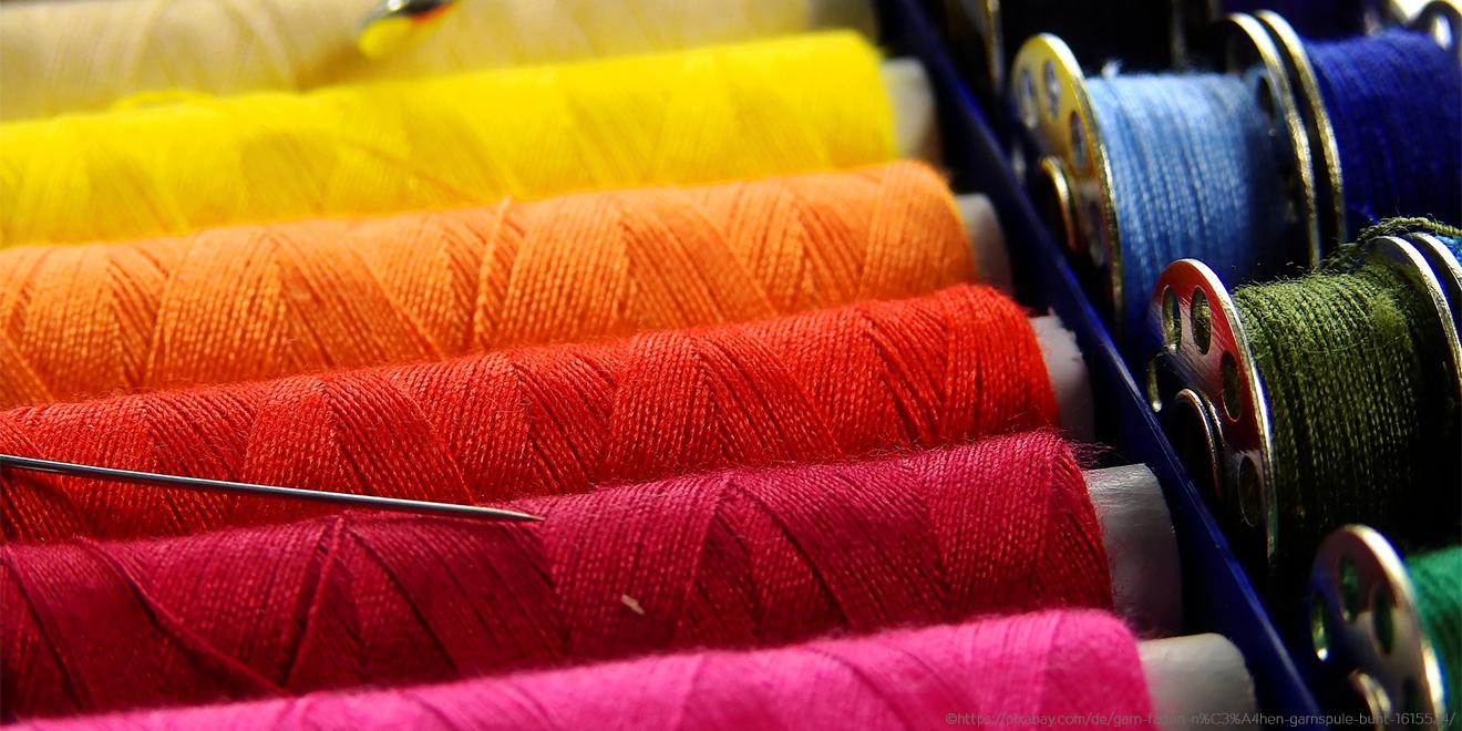 Bunte Fäden und Nadel zum Kleidungsstück flicken