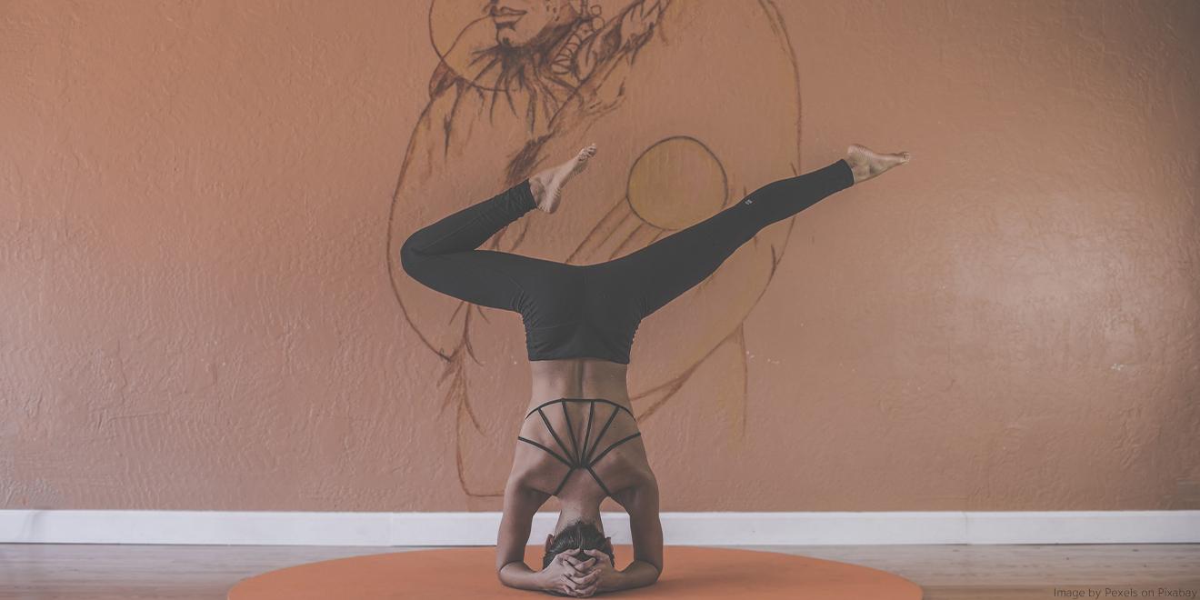 Frau macht akrobatische Yogastellungen um innere Balance für Körper und Geist zu schöpfen