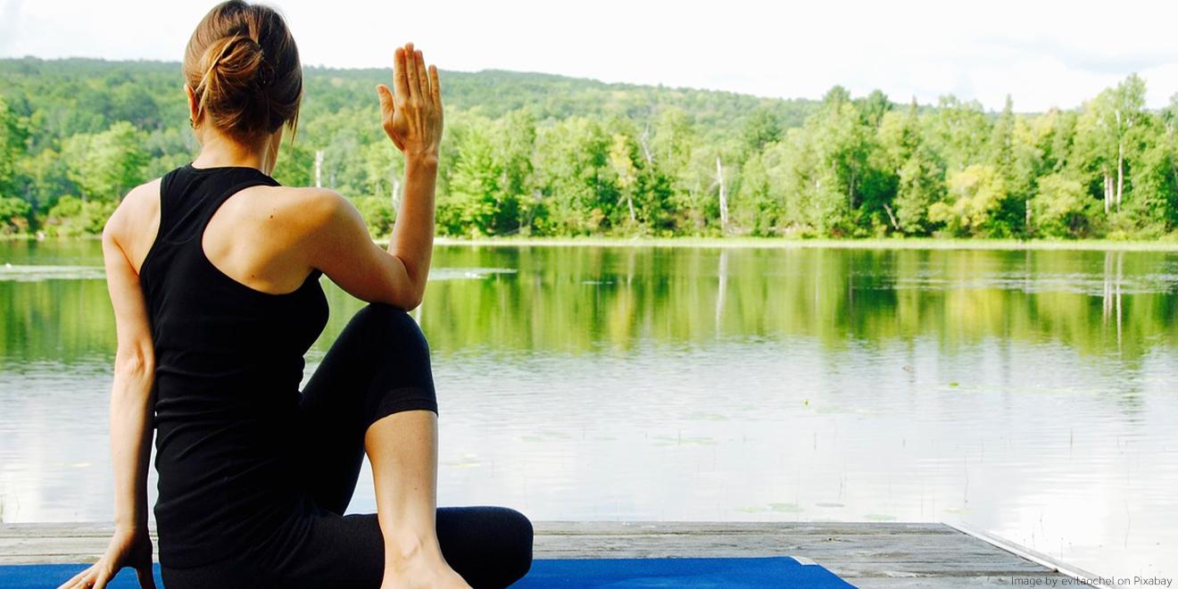"""Frau macht die Yogastellung """"Drehstitz"""" vor einer Seekulisse"""