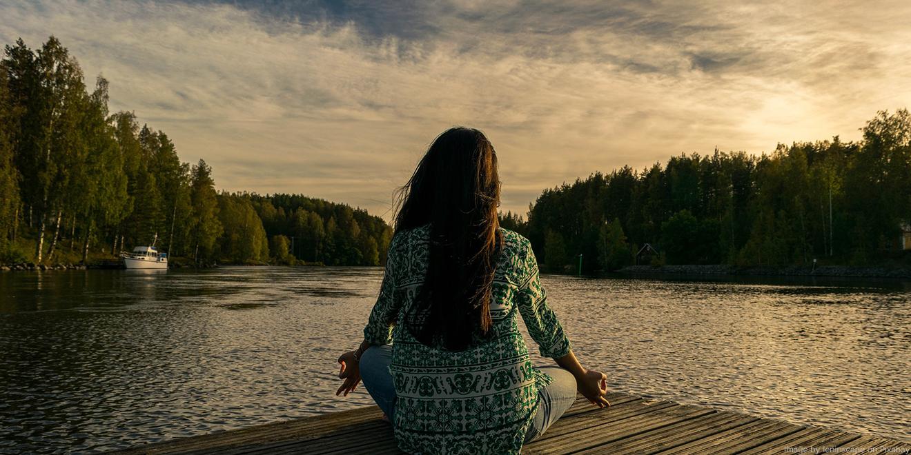 Frau entspannt beim Yoga vor einem Sonnenuntergang