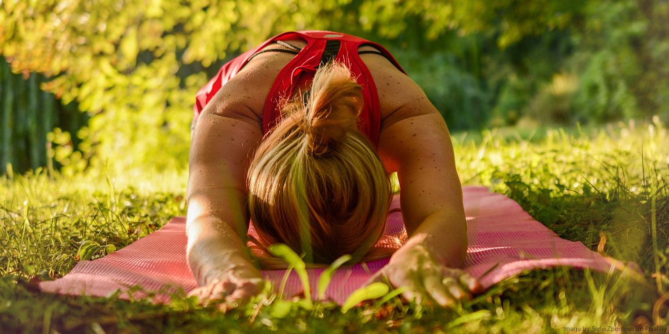 Frau kommt durch Yogastellung zur Ruhe, mitten im Grünen