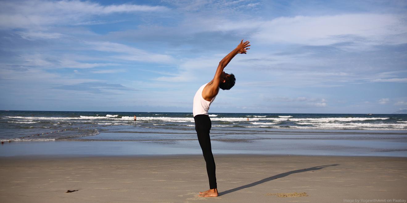 Yogastellungen wie der Sonnengruß stimmen auf die Atmung ein. Herr macht den Sonnengruß am Meer
