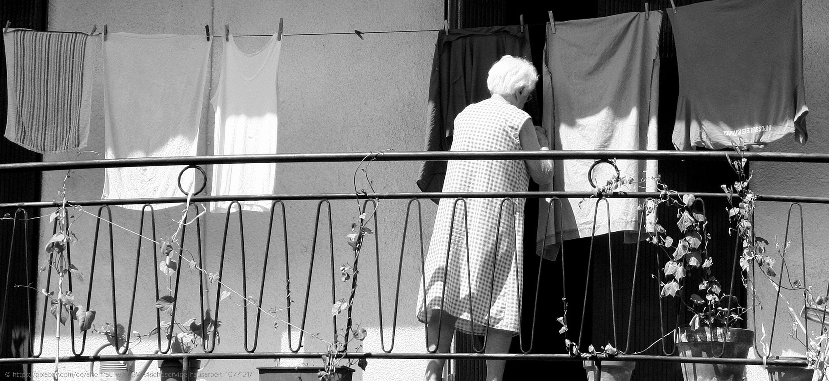 Oma hängt T-Shirts und Unterhemden auf die Wäscheleine