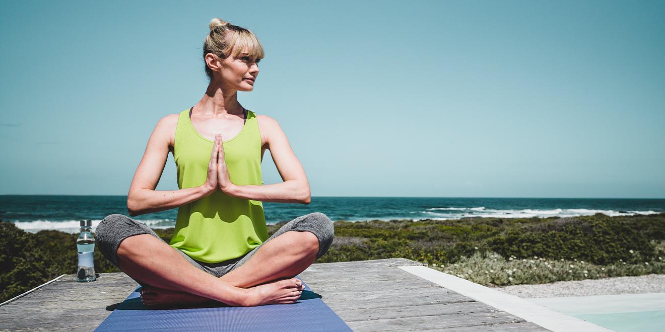 Frau macht Yogastellung vor Seekulisse in TRIGEMA Sportbekleidung