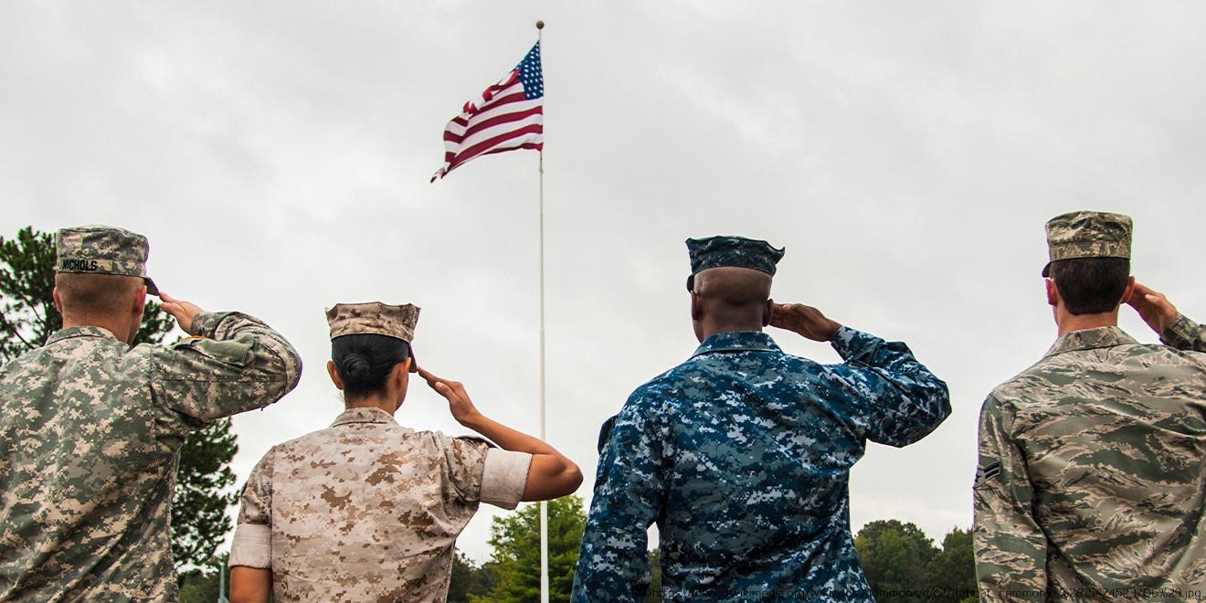 U. S. Soldaten salutieren vor der amerikanischen Flagge und tragen T-Shirt oder Unterhemd unter der Uniform