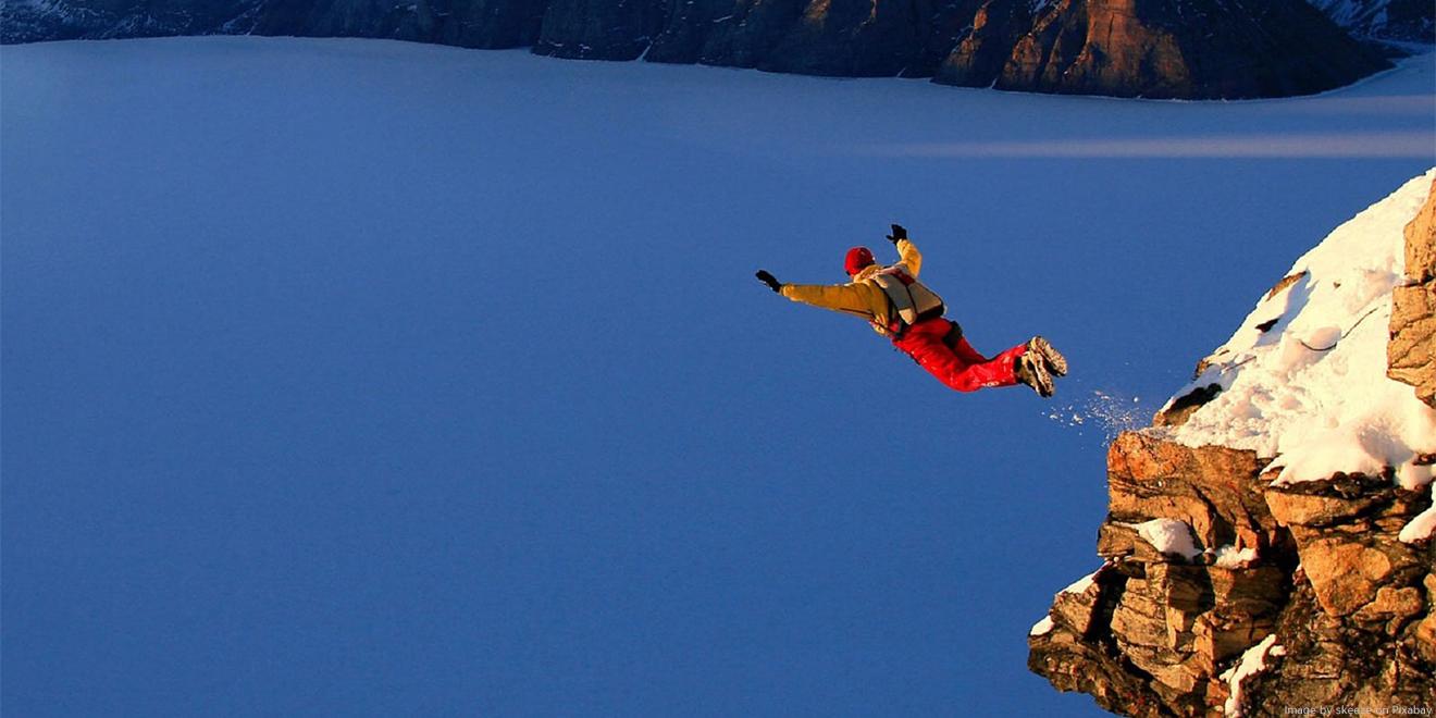 Base Jumper stürzt sich vom Felsen in die Tiefe, mit einem Fallschirm auf den Rücken.