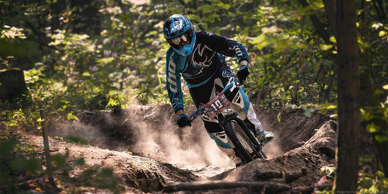 Downhiller rast auf seinem Fahrrad durch den Wald mit Hindernissen und extremer Schutzkleidung/Panzerung