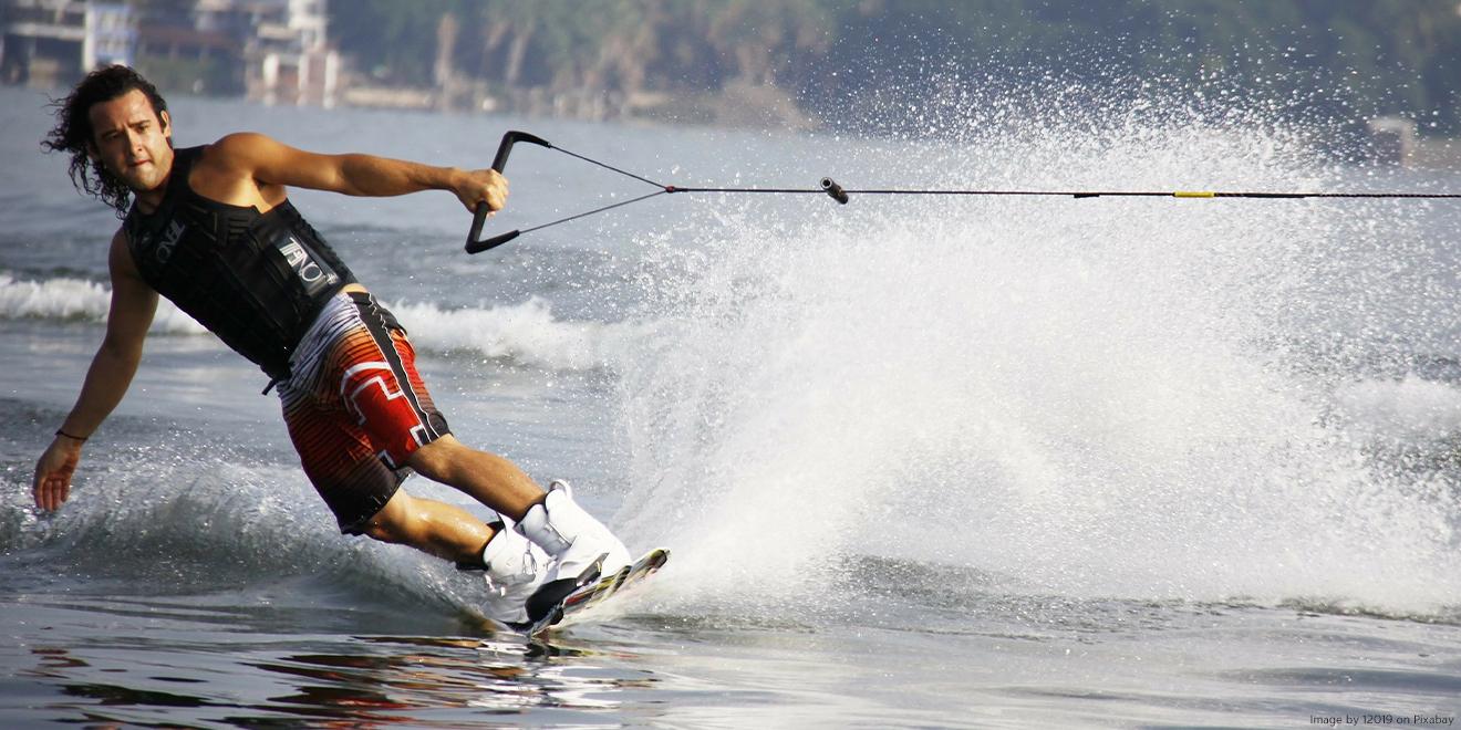Mann auf einem Wakeboard fährt Wasserski