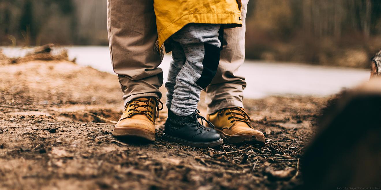 kleines Kind steht mit Elternteil im Wald auf feuchtem Boden. Im Regenmantel entdeckt das Kind Natur und Abenteuer.