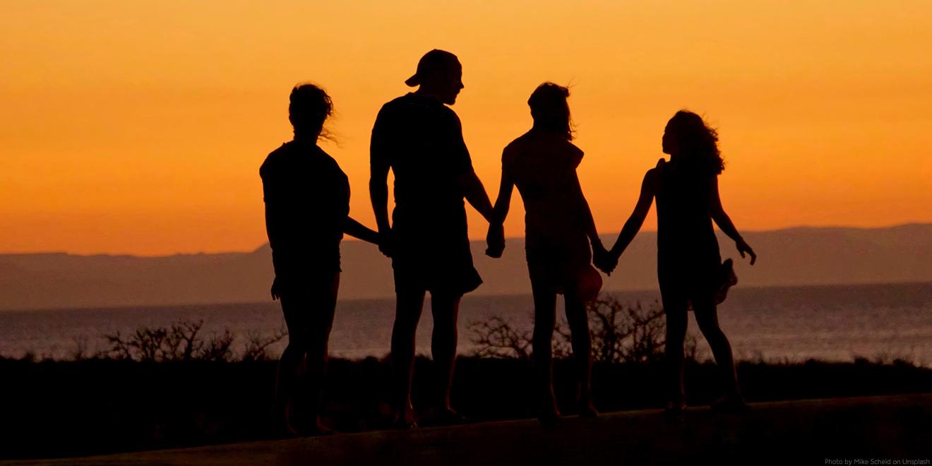 Familie steht gemeinsam am Sonnenuntergang und hebt die Hände. Eltern mit zwei Kindern.