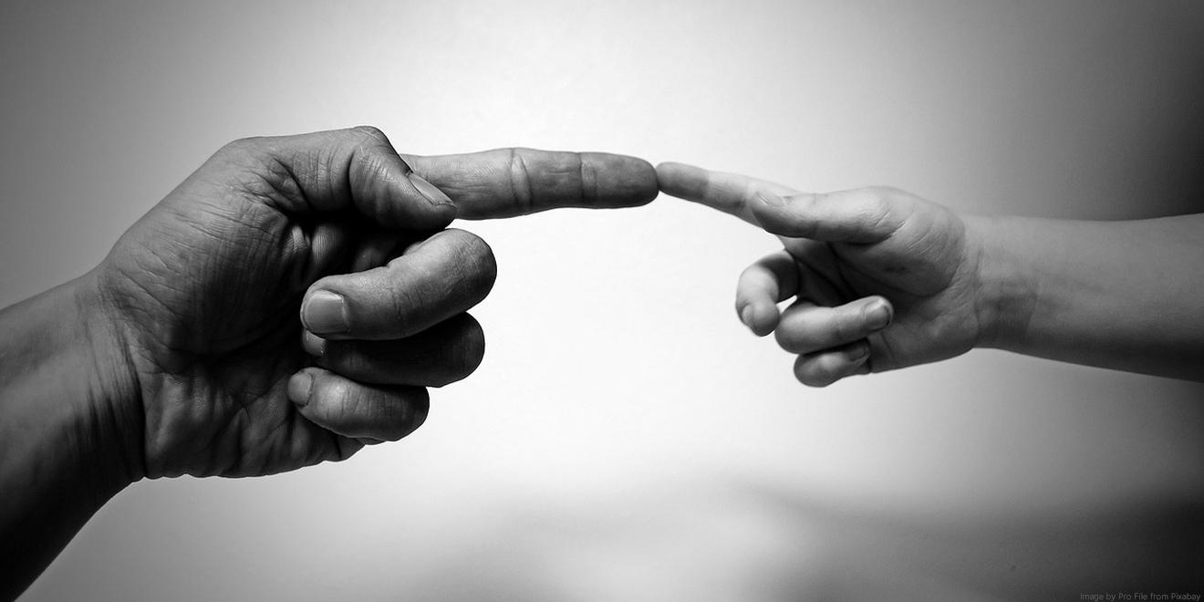 Die Hände von Vater und Sohn oder Tochter berühren sich wie auf dem Bild von Da Vinci in der sixtinischen Kapelle.