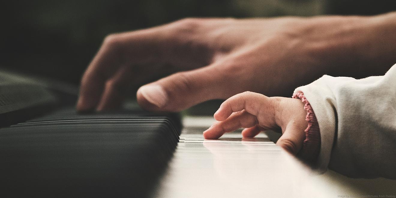 Elternteil bringt Baby oder Kind bei Klavier zu spielen. Eltern sind die Hauptindikatoren für die Talente eines Kindes.