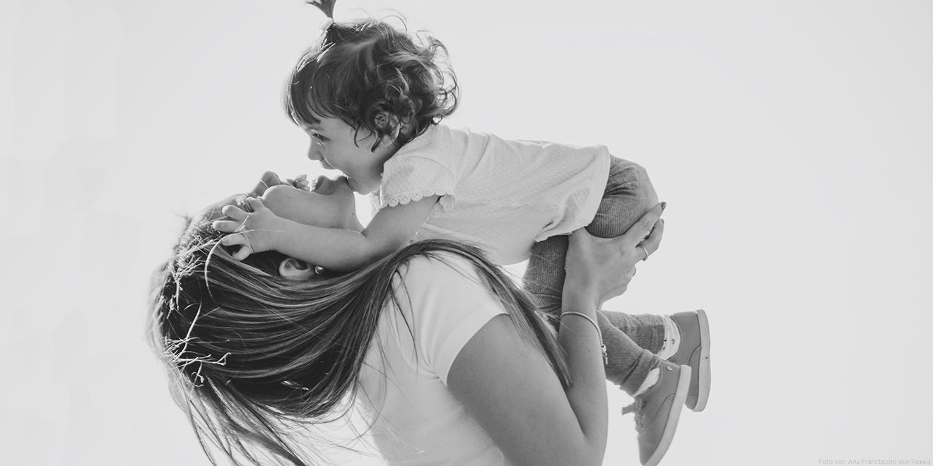 Mama lacht mit ihrer Tochter auf dem Arm. Sie machen Faxen und schenken sich gegenseitig viel Liebe. Genießt den Mutter- und Vatertag!