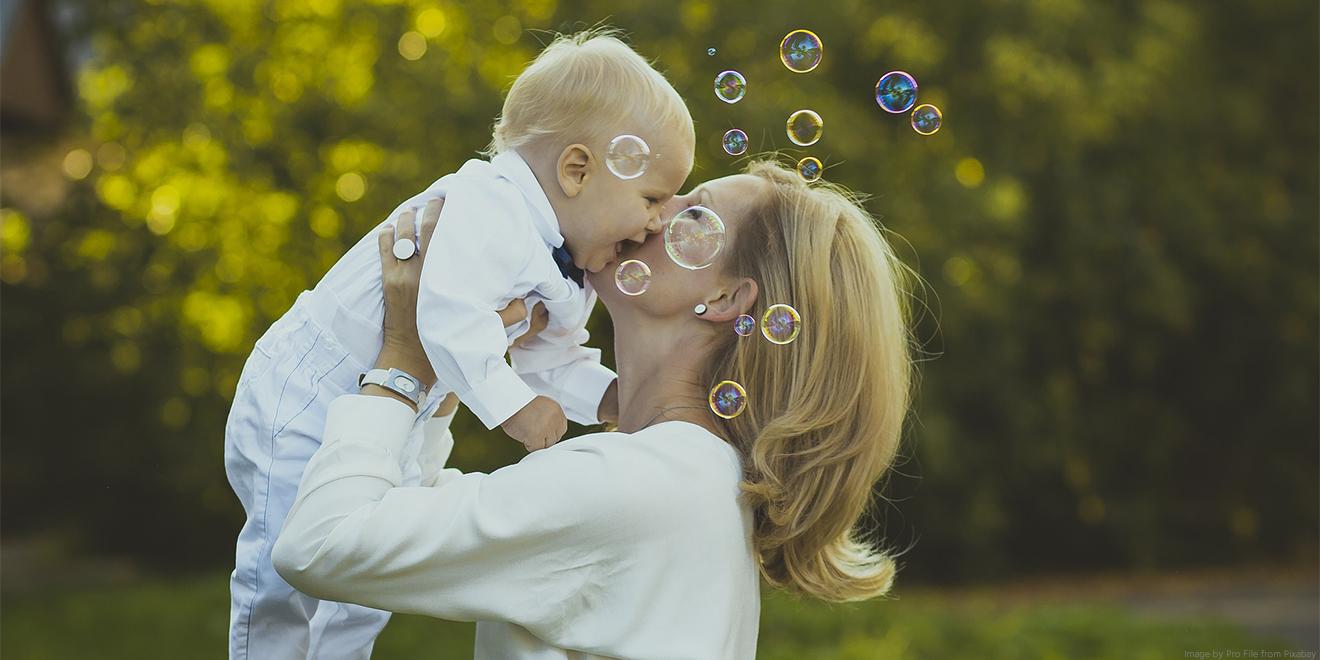 Mutter küsst ihr lachendes Baby. Zum Mutter- und Vatertag werden viele Geschenke gemacht. Lachen und Liebe schenken sind die Schönsten.