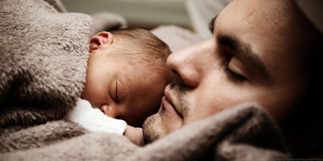 Papa kuschelt mit neugeboreneem Baby im Bett.