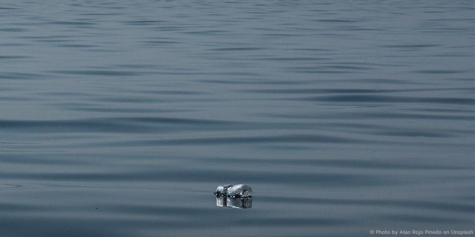 Eine Plastikflasche treibt im Meer