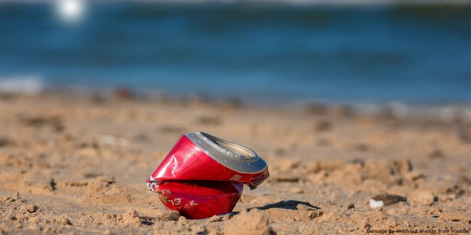 Wird beim Plogging aufgesammelt: Zerbeulte alte Coladose am Strand
