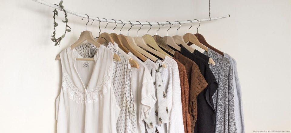 Ein Kleiderschrank mit Kleidungsstücken von weiß über Erdtöne bis Schwarz.