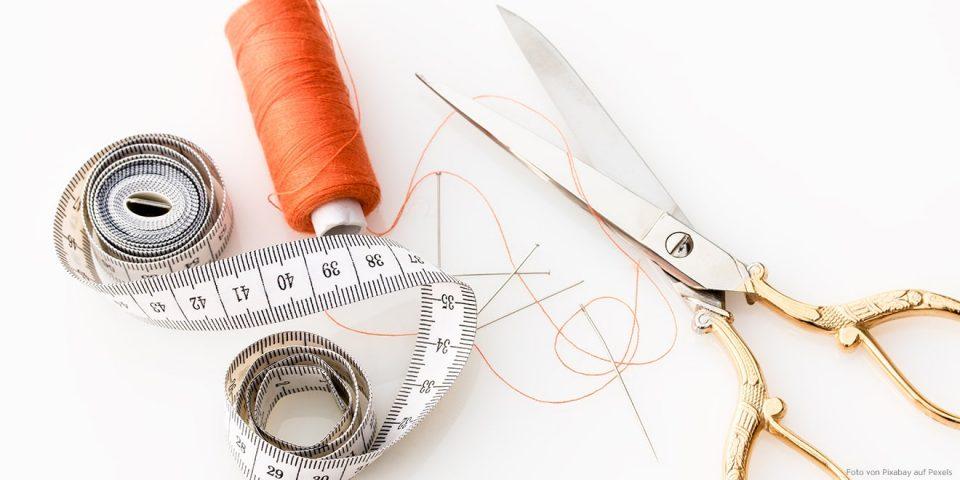 Die Materialien um zu große Kleidung zu Lang- und Kurzgrößen anpassen: Schere, Maßband und Garn.