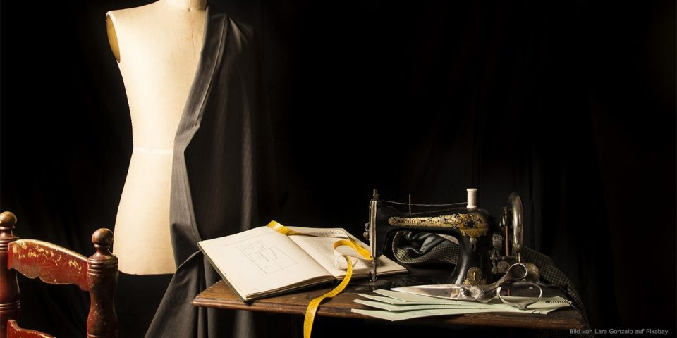 Atelier eines Änderungsschneiders, mit Puppe, Tisch, Nähmaschine und Buch.