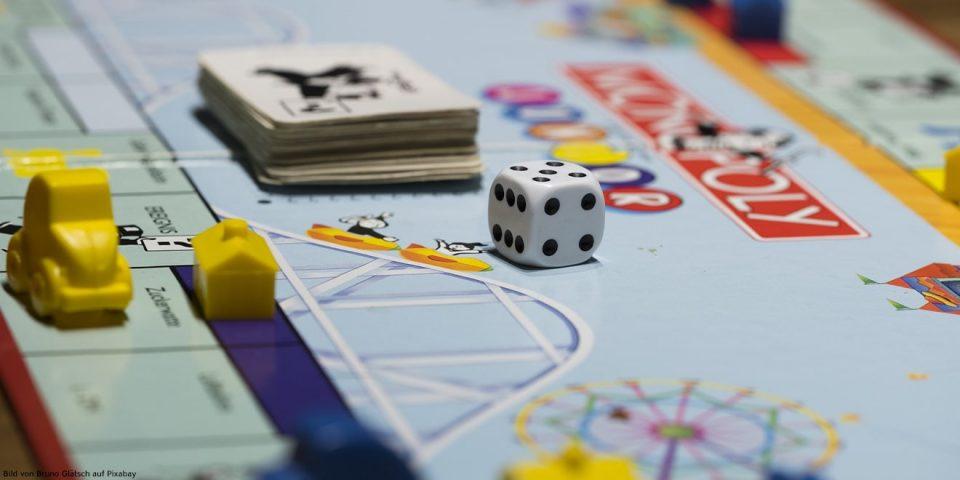 Würfel und Spielfiguren liegen auf einem Gesellschaftsspiel