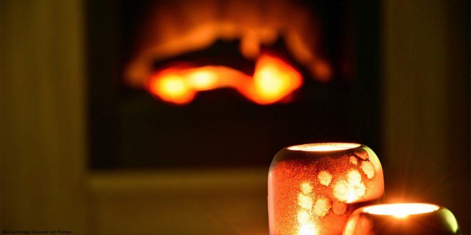Kerzen vor einem Kaminfeuer