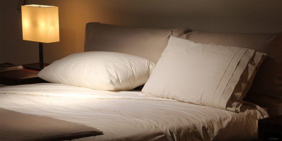 Leeres weißes Bett mit Lampe und Buch zum schlafen und lesen