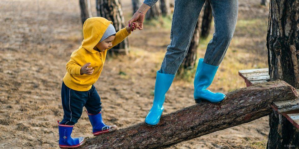 Mama hilft Kind über einen Baumstamm laufen. Soziale Selbstpflege bedeutet auch Persönlichkeitsentwicklung