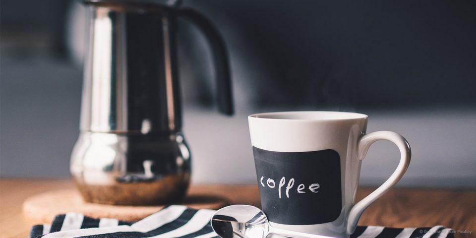 Kanne und Tasse Kaffee auf dem Tisch für eine Pause