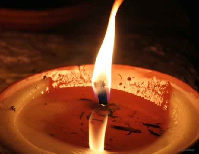 Brennende Kerze mit angesammeltem Kerzenwachs