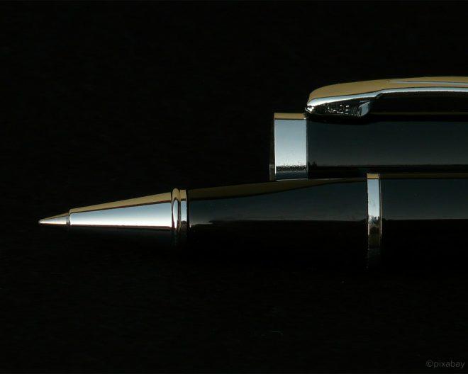 Offener Kugelschreiber auf schwarzem Hintergrund