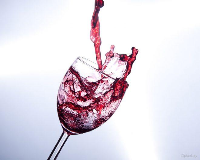 Glas mit Wein kurz vor dem umfallen