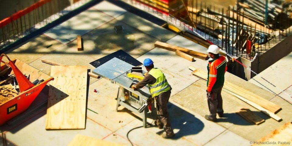 Bauarbeiter arbeiten am Bau mit schweren Materialien und Geräten.